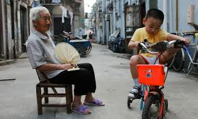 ElderlyAsian woman watching her grandson riding his bike